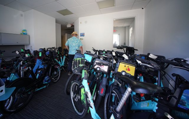 Biki Executive Director Todd Boulanger walks into the entrance of Biki offices in Kakaako filled with damaged bikes.
