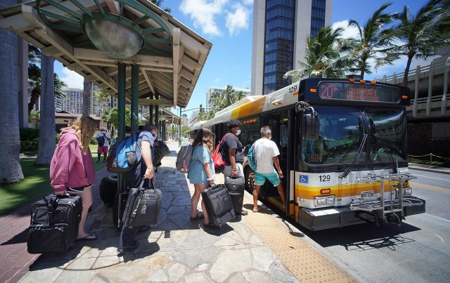 Passengers board TheBus route 20 with luggage on its way to the Daniel K. Inouye International Airport from Waikiki.