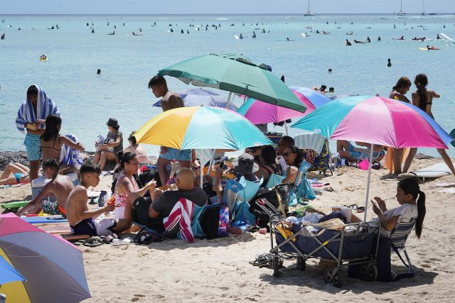 People gather under umbrellas near Kuhio Beach during COVID-19 pandemic.