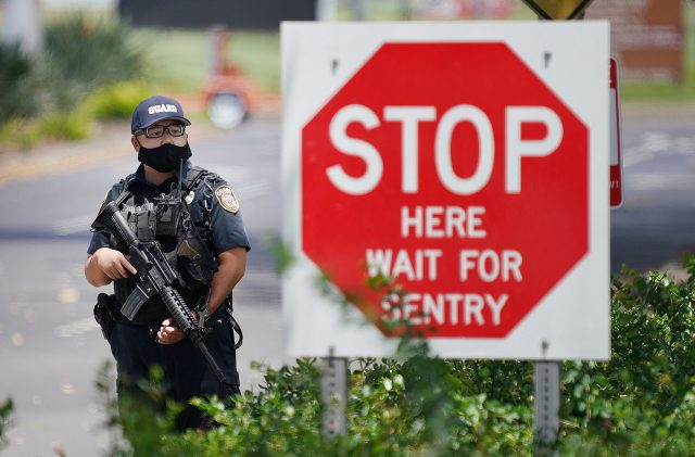 Armed guard stands with assault rifle at Joint Base Pearl Harbor Hickam, Makalapa Gate during a base lockdown.