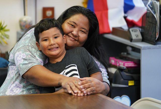 Jennifer Nakamura embraces her son Hisao (she declined on last name) at 46-005 Kawa Street in Kaneohe.