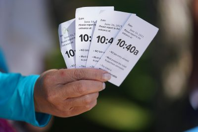 Hanauma Bay visitors hold their tickets with the entrance times.
