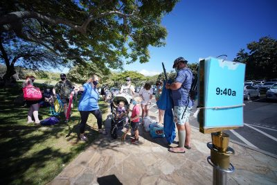 Hanauma Bay visitors stand near a sign that shows entrance appointment times.
