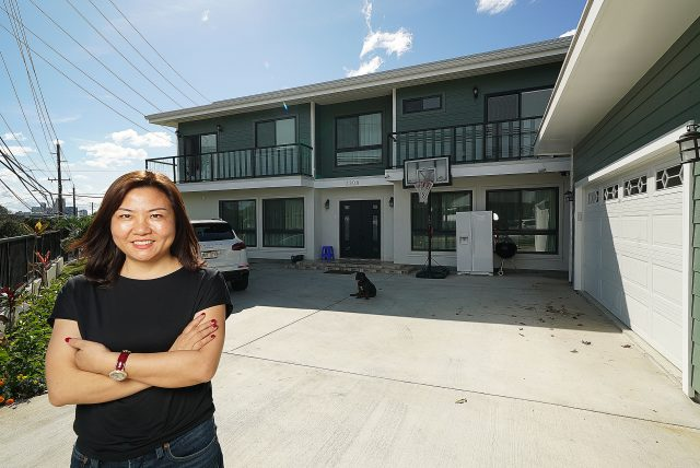 Christy Zeng Lei stands fronting one of houses she owns located at 2308 Dole Street.