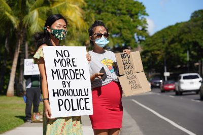 Cassie Chee and right, Cathy Lee hold signs in opposition to police shootings fronting Honolulu Hale with scores of others.