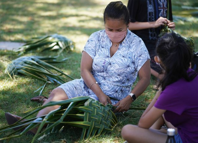 Board of Education member Shanty Asher assists Washington Middle School students with weaving coconut frond baskets.