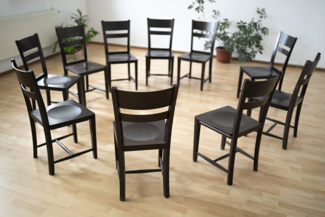 A circle of empty chairs in a plain room with a wooden floor