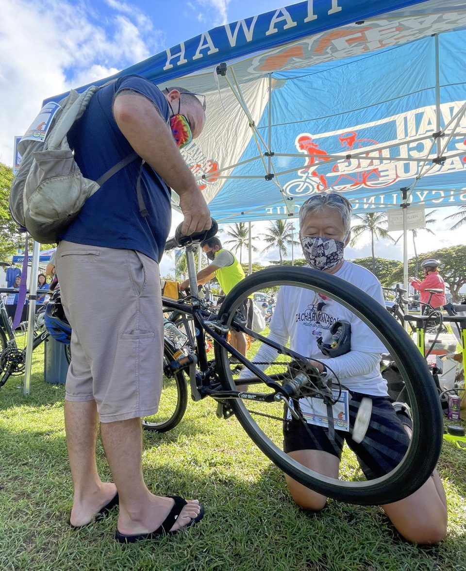Roger Au, right, helping a participant fix his bike before Zach's Ride In Paradise, in honor of the late Zach Manago's legacy and vision of bike safety. (Photo: Ronen Zilberman/Civil Beat)