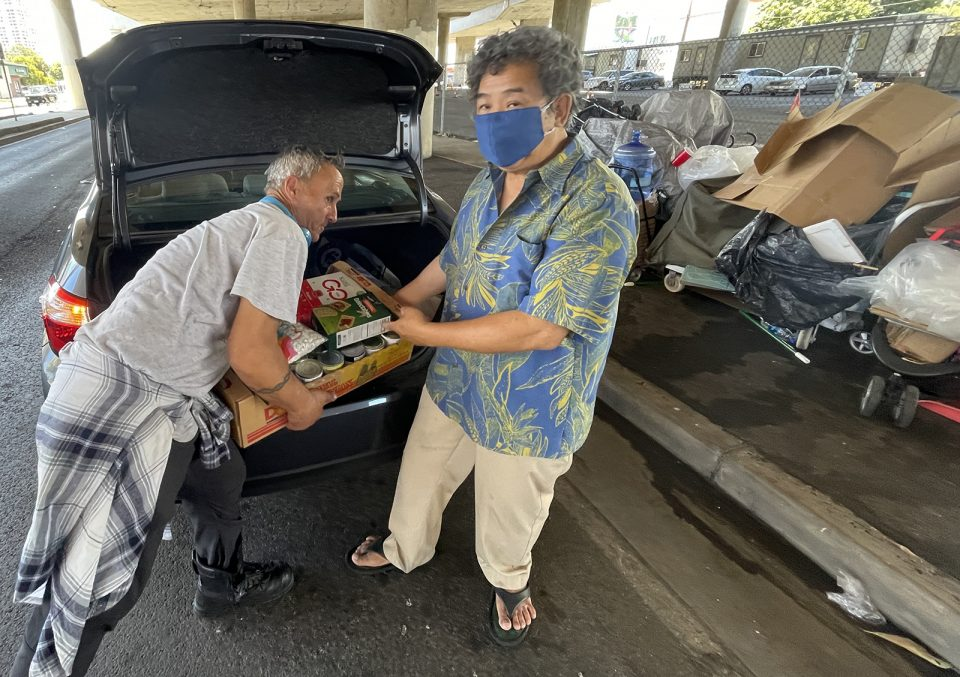 Bill Sheen distributes food he bought with his own money to a group of homeless individuals beneath the H1 freeway overpass at Kapahulu Blvd in Honolulu, on Wednesday, July 14, 2021. Sheen says he performs these acts of kindness on a daily basis. (Ronen Zilberman photo Civil Beat)