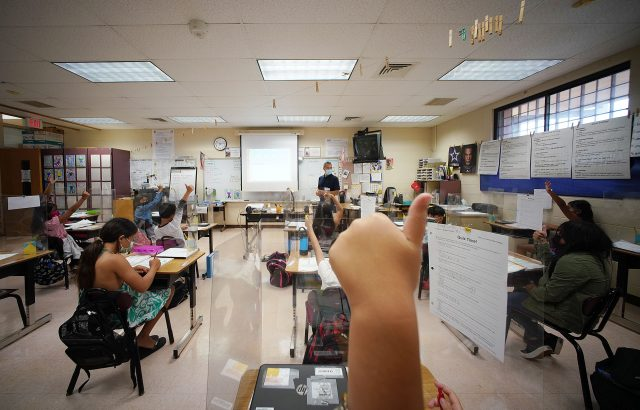 A student raises their thumb at Holomua Elementary School in Mr. Suan's 4th grade class.