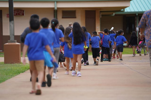 Holomua Elementary School students walk back to their classrooms after recess.