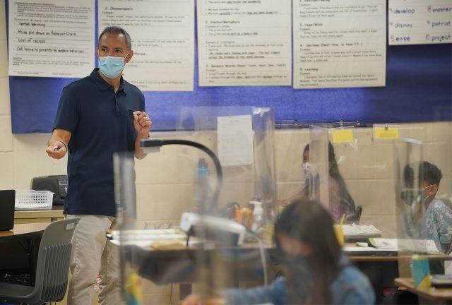 Holomua Elementary School 4th grade teacher, Mr. Suan, teaches students.