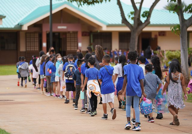 Holomua Elementary School students line up after recess.