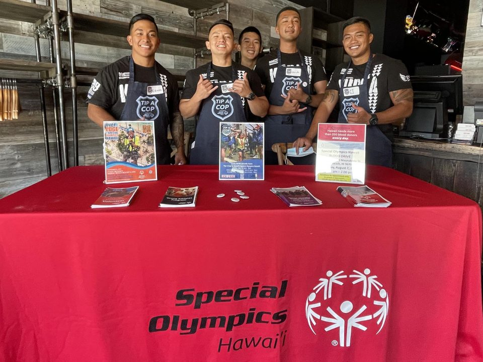 """Honolulu police officers, from left, Edison Tagama, Garrison Gamio, Keenan Kihara, Uriah Simmons, and Christopher Oallasma volunteer to greet customers and assist servers at Lucky Strike, in the Ala Moana Shopping Center, to raise awareness for Special Olympic Hawai'i athletes, Sunday, July 18, 2021.  All proceeds raised from the """"Tip a Cop"""" event will stay in the islands to help fund sports training, competitions, and programs for local athletes. (Ronen Zilberman photo Civil Beat)"""