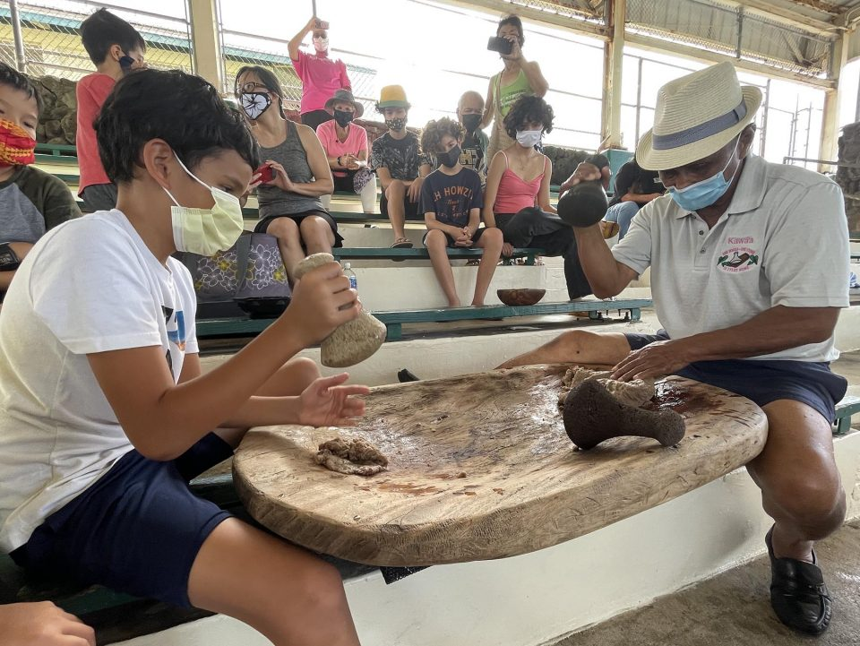Kumu Earl Kawaa (right) passes down the Hawaiian tradtion of poi pounding (ku'i kalo) to Kaimalu Pomroy (left) and other participants during the Lā Ku'i Kalo I Papakōlea in Honolulu, Hawaii. Saturday July 24, 2021.  Like many other participants the Pomroy family appreciates the opportunity Papakōlea is providing for them to use their board and stones to make poi as a means to reconnect with their family, culture, community and the aina. (Ronen Zilberman photo Civil Beat)