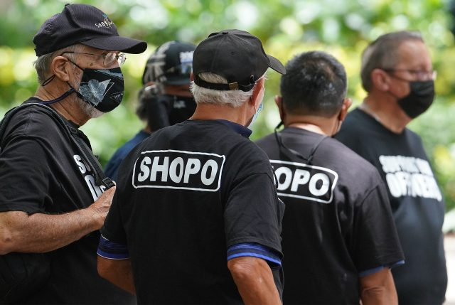 HPD supporters wearing SHOPO shirts stand outside District Court during a preliminary trial in Judge Domingo's courtroom.