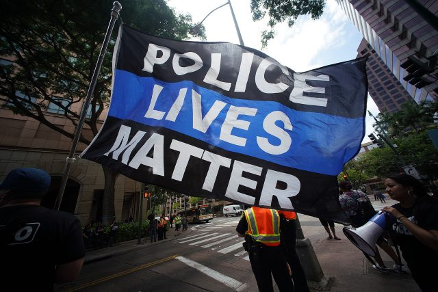 """An HPD supporter holds a large flag that reads, """"Police Lives Matter' fronting DIstrict Court."""
