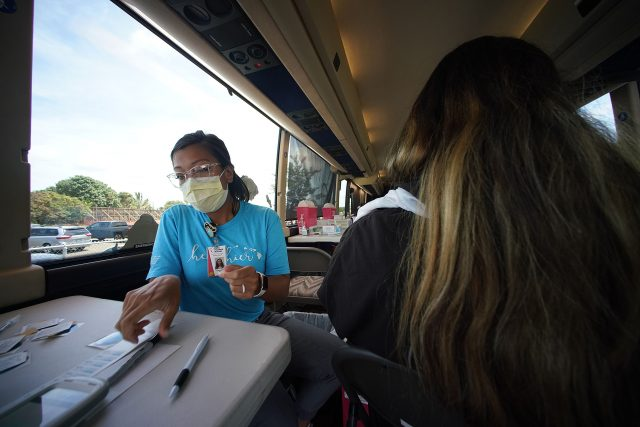 Crystal Alfonso RN assists in giving vaccinations at Ilima Intermediate School on the HPH vaccination bus.