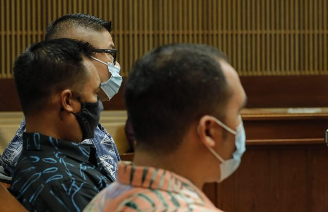 Honolulu police officers Geoffrey Thom, top, Christopher Fredaluces, and Zackary Ah Nee sit in the district courtroom of judge William M. Domingo during the second day of preliminary hearings for three Honolulu police officers in the killing of Iremamber Sykap on Tuesday, July 27, 2021, in Honolulu. (POOL PHOTO/Jamm Aquino/Honolulu Star-Advertiser).