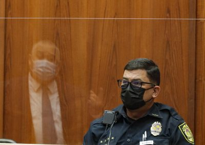Honolulu police Sgt. Adam Lipka listens to questions from defense attorney Richard Sing, reflected in the plexiglass barrier, in the district courtroom of judge William M. Domingo during the third day of preliminary hearings for three Honolulu police officers in the killing of Iremamber Sykap on Tuesday, July 27, 2021, in Honolulu. (POOL PHOTO/Jamm Aquino/Honolulu Star-Advertiser).