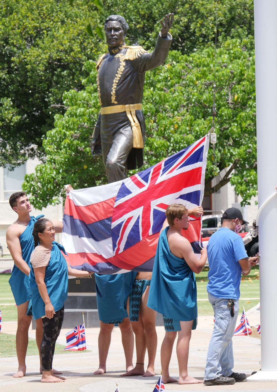 """Hawaiian flag being raised at Thomas Square Park in Honolulu on July 31, 2021. At the start of the """"Lā Hoʻihoʻi Ea Honolulu"""" also known as Hawaiian Restoration Day. Comemmorating the return of the Hawaiian Kingdom's Sovereignty from Britain 178 years ago. Photo/Ronen Zilberman Civil Beat"""