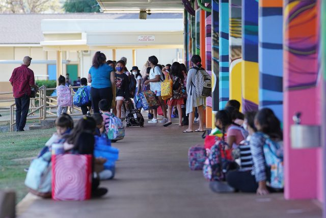 Students at Aliiolani Elementary School wait outside classrooms before the start of the first day of school during a COVID-19 pandemic.