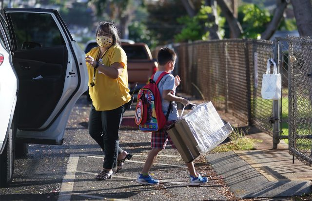 Waialae Elementary Public Charter school staff Melanie Sumida assists with arriving students. Waialae Elementary started last week.