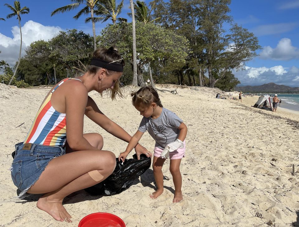 Emily Robenolt visiting from Pennsylvania and her niece Makenna Ptaszek from Kailua picking up litter at the Kailua Beach Park cleanup hosted by San Lorenzo bikinis on Sunday August 8, 2021. Ronen Zilberman Civil Beat