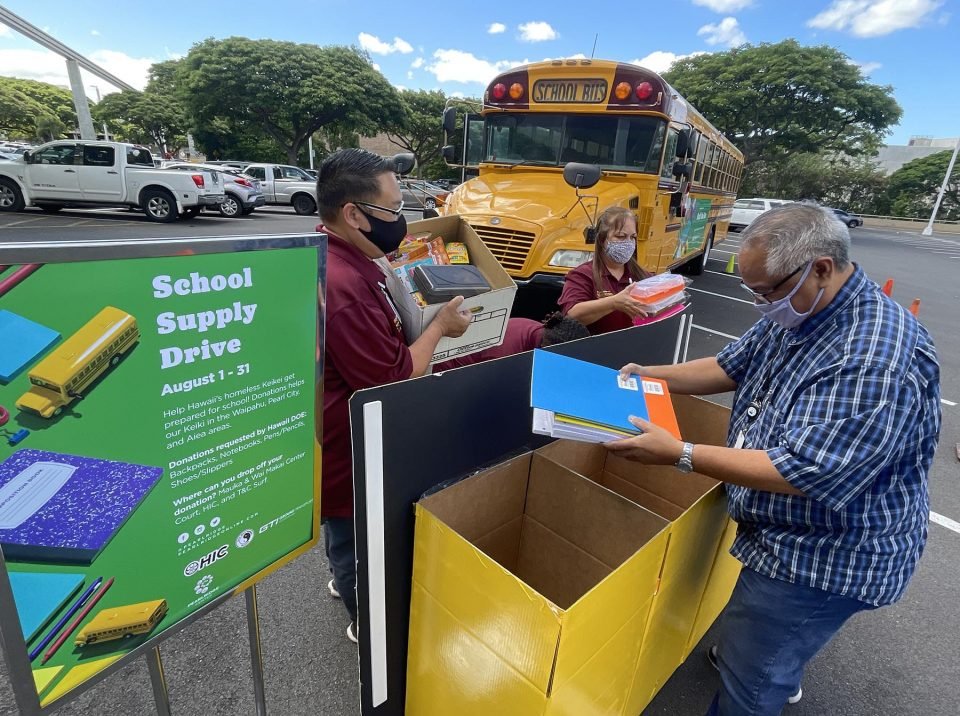 """From left, William Rash, Betty Cuarisma, and Anthony Valiente from Ground Transport Inc. unload school supply donations, from the community, into a display container at the Pearlridge Center, Monday, August 9, 2021. Throughout the month of August the Pearlridge Center will be partnering with Ground Transport Inc. to """"stuff the bus"""" with new school supplies and footwear for students in need. Donations will be distributed to students enrolled in public schools around the Aiea, Pearl City, Waipahu and Kapolei complex areas. (Ronen Zilberman photo Civil Beat)"""
