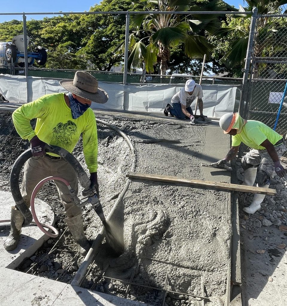Workers lay concrete to build new ramps, as part of a community-led improvement project to upgrade the skate park at Kailua District Park, on Monday, August 9, 2021. The project is being funded and spearheaded by the Association of Skateboarders in Hawai'i (ASH), who are donating the design, materials, and construction of the skate park upgrades at a cost of nearly $130,000. (Ronen Zilberman photo Civil Beat)