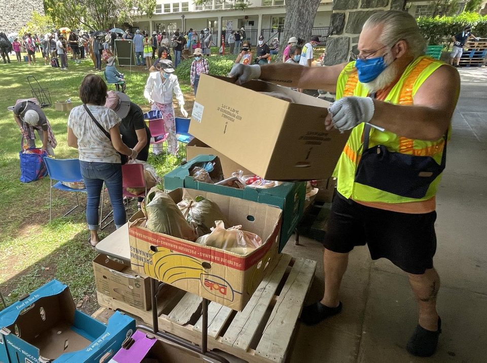Gary Hoover stacks boxes of food donations while volunteering at Central Union Church in Honolulu, Wednesday, August 11, 2021. At least a hundred people, from around the community, showed up to receive boxes of food. (Ronen Zilberman photo Civil Beat)