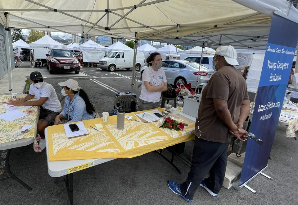 Volunteers from the Ask-a-Lawyer-Booth (from left) Lansen Leu, Therese Oriola, and Sharon Paris, offering offer free legal information, and educating people on various areas of the law, during the annual Law Week event at Kakako Farmers Market in Honolulu Saturday August 14 2021. Ronen Zilberman/Civilbeat
