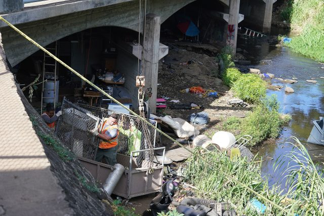 City workers help clean up the homeless camp under a bridge under Kapiolani Boulevard / Manoa Palolo Drainage Canal.  This area is located in front of Kaimuki High School.