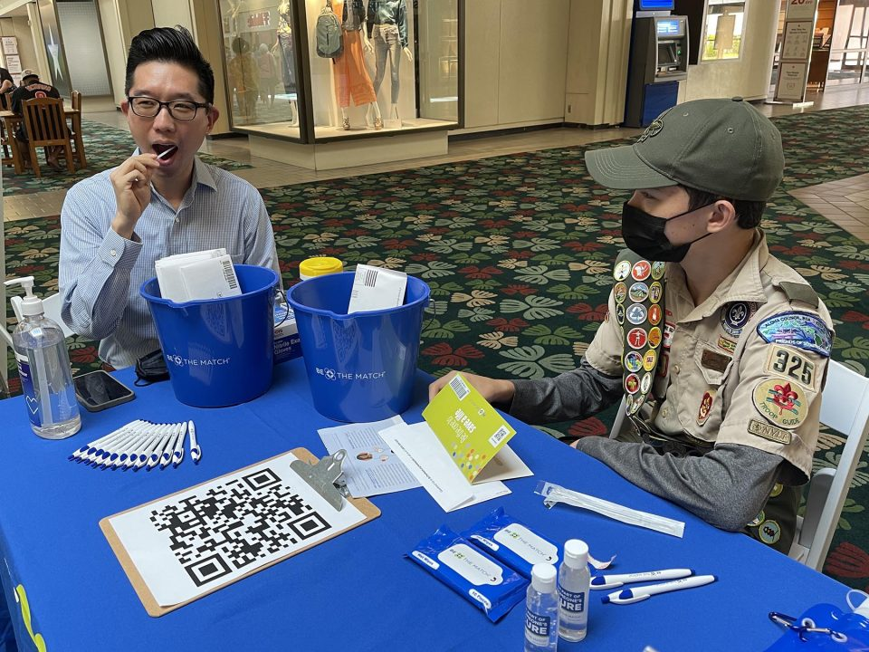 """Hawaii State Senator, Stanley Chang (left) swabs his mouth as part of the process to become a bone marrow donor during a donor match drive organized by Eagle Scout troop 325 member Riley Regan (right), at the Kahala Mall, Friday, August 20, 2021. Regan was inspired by his dad's experience becoming a bone marrow donor to organize the drive, for his Eagle Scout project. His goal is to register 1,000 new people  with Be The Match Hawaii. Regan has organized donor match events across the islands throughout the months of August and September. """"Although we are all focused on COVID-19 and the high case counts, there are both kids and adults whose future to live depends on finding a match,"""" Regan said. (Ronen Zilberman photo Civil Beat)"""