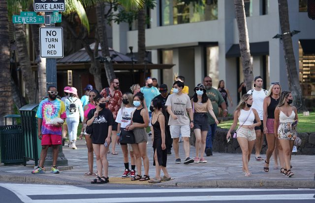 People wait at the intersection of Kalakaua Avenue and Lewers Street during a recent surge in Covid-19 cases. August 22, 2021
