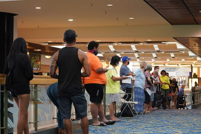People wait in line outside a Covid-19 vaccination site located at Windward Mall on August 24, 2021.