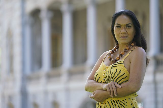 Portrait of Starr Kalihiki with Iolani Palace in the background.