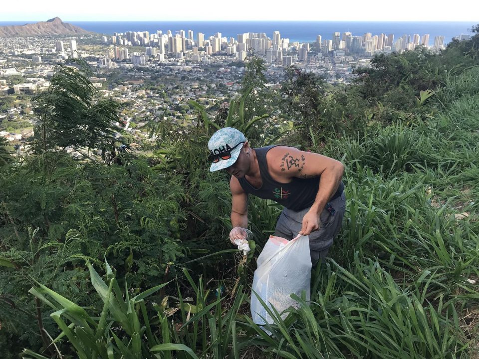 Nick Freitas takes a moment to pick up rubbish from a scenic overlook on Tantalus Drive in Honolulu, while there to watch the sunset, Saturday, August 28, 2021. (Ronen Zilberman photo Civil Beat)