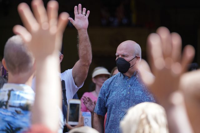 Unmasked members from the Aloha Freedom Coalition raise their hands to ask Mayor Rick Blangiardi questions fronting Honolulu Hale.