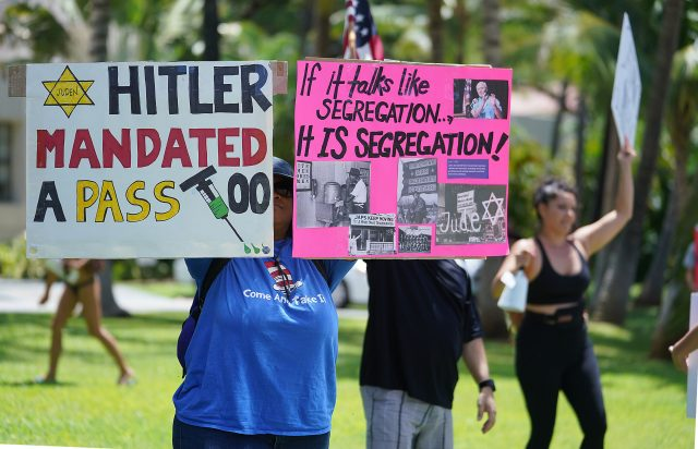 Anti Covid-19 Vaccination demonstrator holds a sign with a reference to Hitler while demonstrating outside Honolulu Hale.