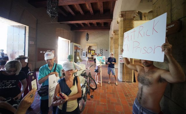 Demonstrator holds a sign 'Put Rick in Prison' inside Honolulu Hale. Honolulu Police officers were on the scene during a council meeting.