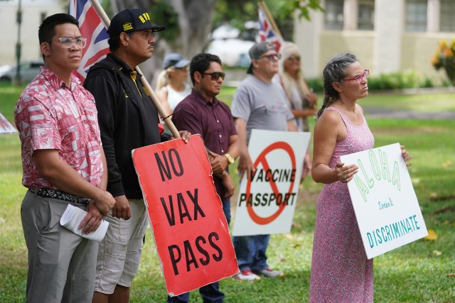 Supporters from KOA and the Aloha Freedom Coalition hold signs during a press conference held at Honolulu Hale.