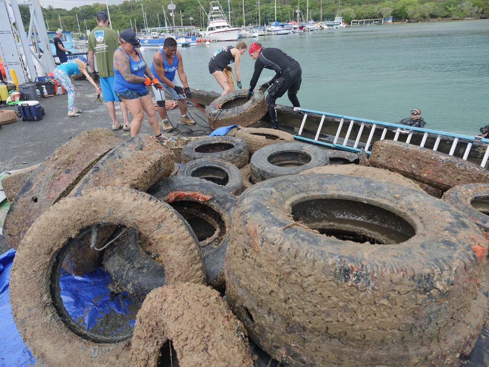 volunteers for the Ocean Defenders Alliance (ODA) pull an old tire out of the water at the Kaneohe Harbor, Sunday, September 12, 2021. The group of ODA volunteers retrieved 43 tires from around the dock of the Harbor Master in Kaneohe Bay. (Ronen Zilberman photo Civil Beat)