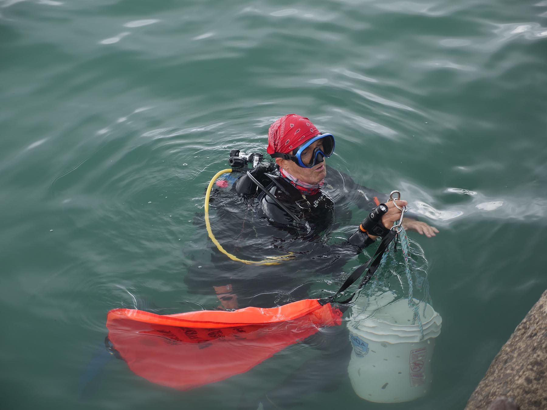 <p>Glenn Roberts brings a bucket of debris up from the ocean floor to the surface to hand off to ground crew volunteers.</p>