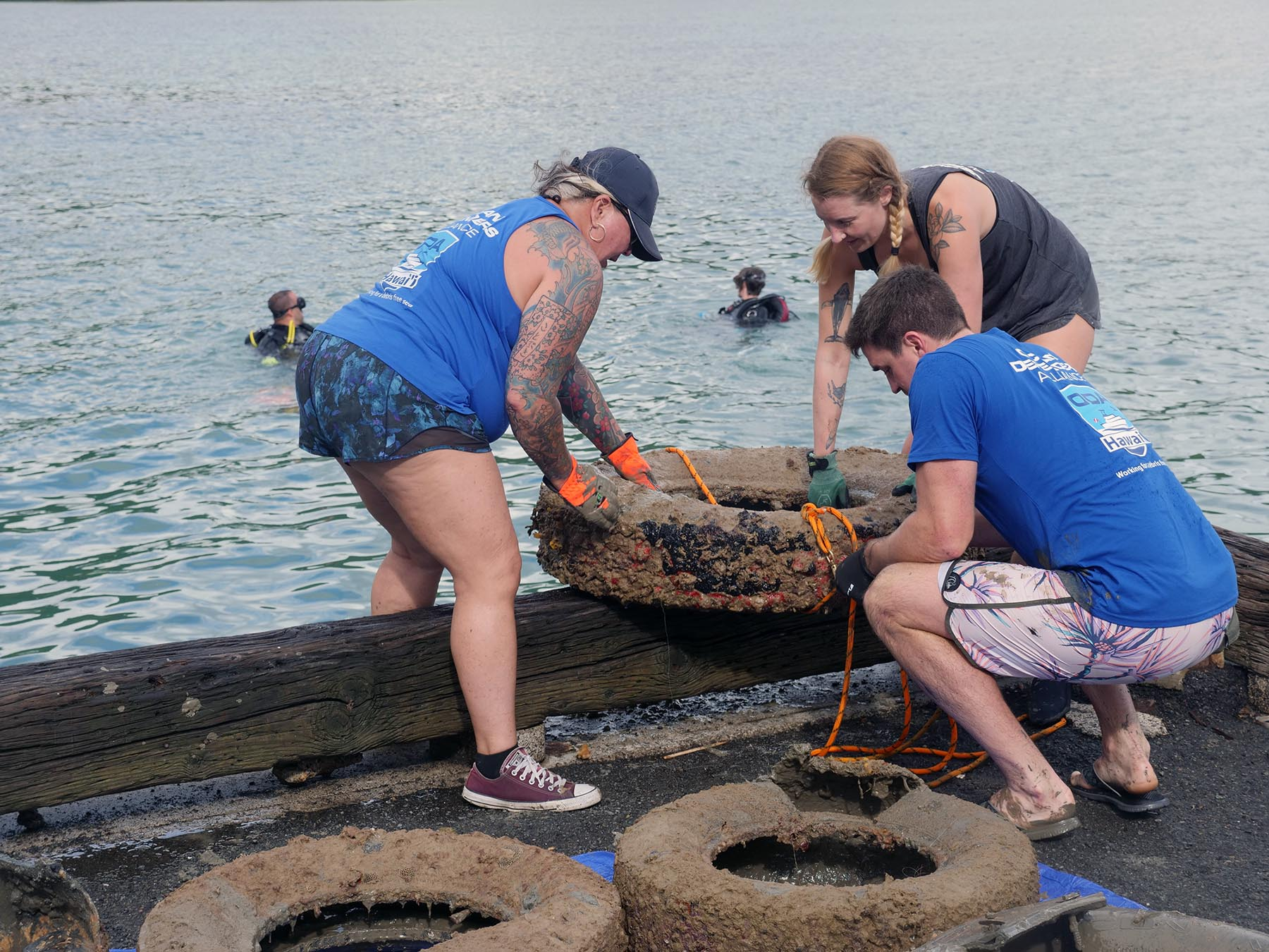 <p>Kaneohe Bay Harbormaster Tanya Borabora works with Ocean Defense Alliance volunteers Sophie Morgan and Garrett Cook to haul tires retrieved by divers on to the dock.</p>