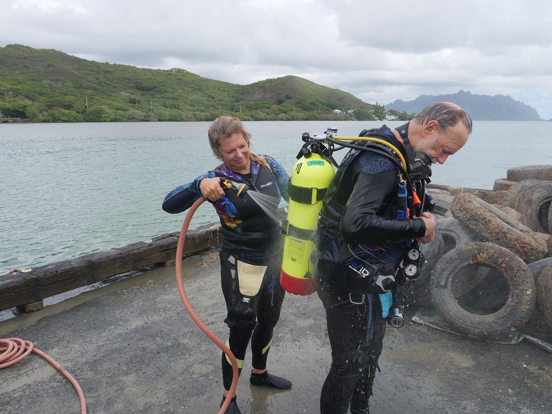 <p>Marjorie Zensen sprays off her husband Mark England after the cleanup dive.</p>