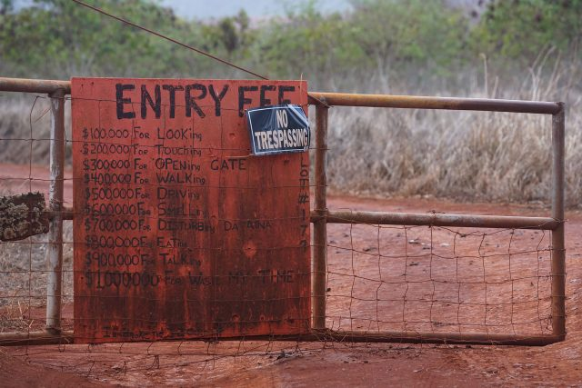 Interesting sign outlining prices for getting thru gate. $100,000 for looking inside on a gate in the DHHL Hawaiian homestead properties near the Molokai Airport.