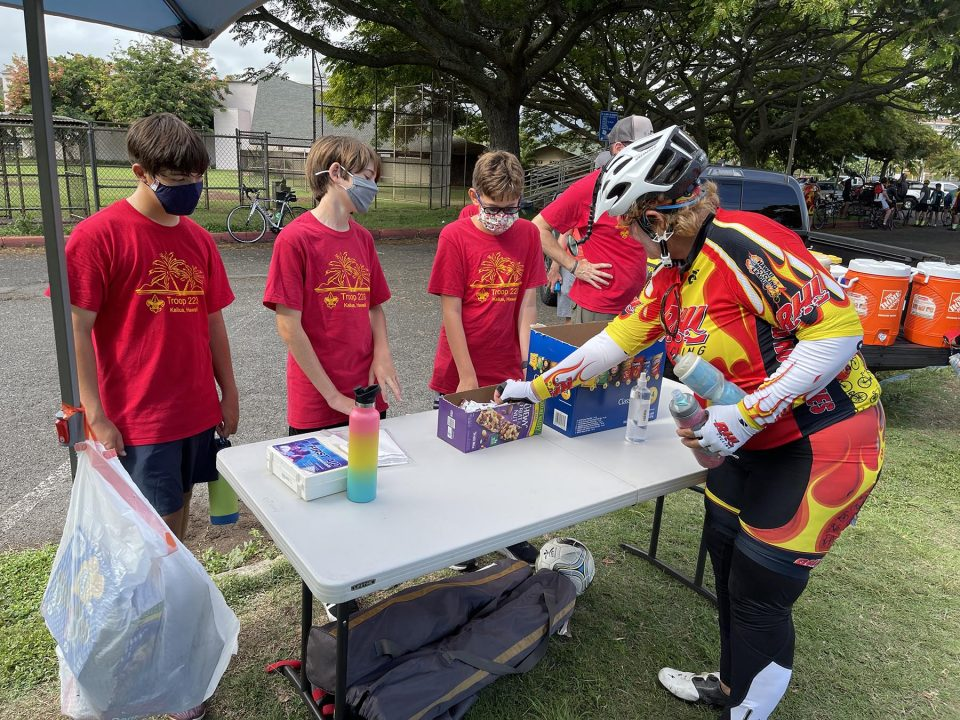 Volunteers from the Boy Scout Troop 223 (from left) Luke Takakuwa-Holtey, Reed Snyder, and Austin Holmquist provide refreshments to cyclists, from the Honolulu Bicycle League's (HBL) 2021 Century Challenge ride, at the Kailua District Park, Sunday, September 26, 2021. HBL organized refueling stations with groups of volunteers for Century Challenge participants who designed their own riding courses in increments of 25, 50, and 100 miles. (Ronen Zilberman photo Civil Beat)