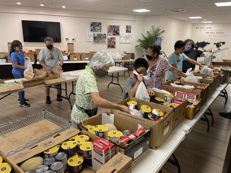 Volunteers for Komo Mai Community Services, part of Leeward Community Church, pack boxes of food for their Take-Away Meals effort in Pearl City, on Tuesday, October 5, 2021. The weekly Take-Away Meals food pantry provides emergency food relief for those in need. (Ronen Zilberman photo Civil Beat)