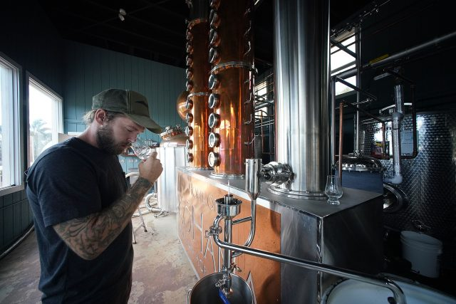 Hawaiian Agricultural Rum Distillery Kohana manager Tyler Johnson stands with the